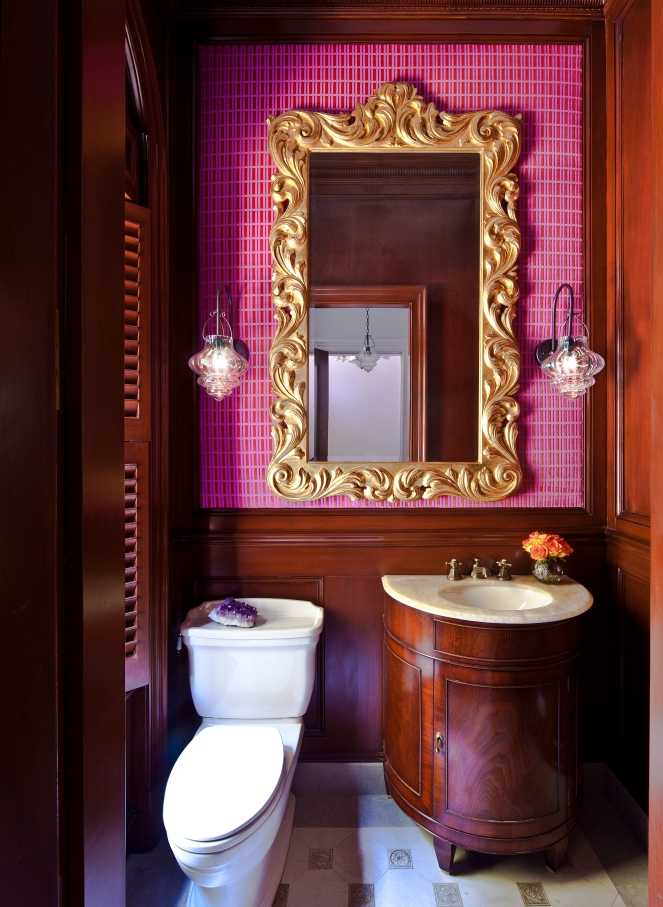 Powder room with traditional wood panelling and gilt mirror, and pink velvet wallpaper, designed by Guillaume Gentet.